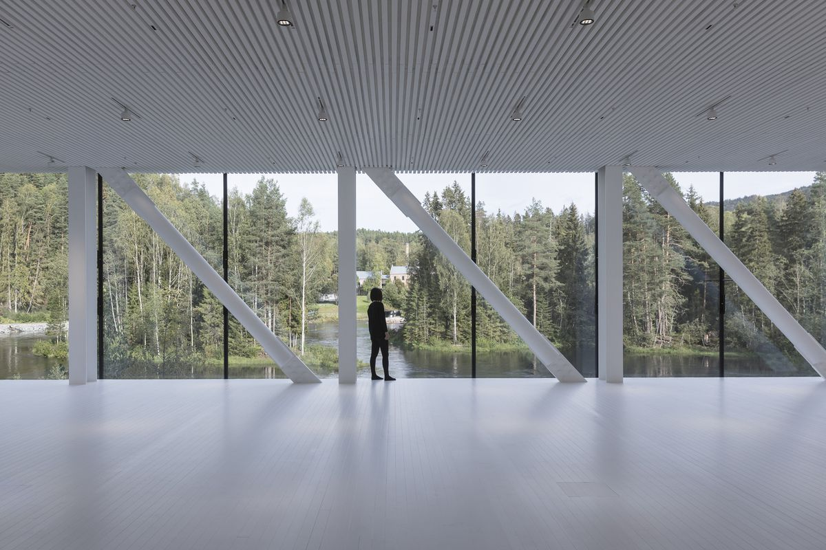 Woman standing in front of large full height windows with river and forest views.