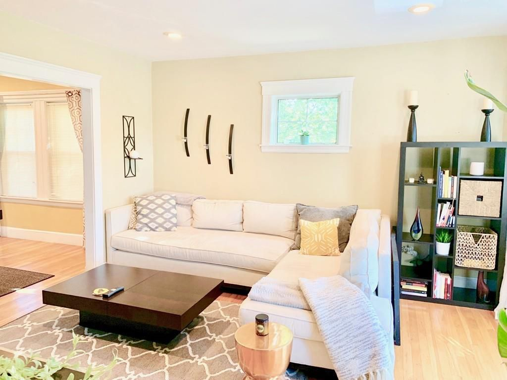 A small living room with a sectional couch around a coffee table.