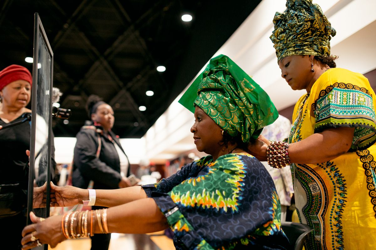 Roseline Onwenu wraps the gele on a woman at the Headwrap Expo.