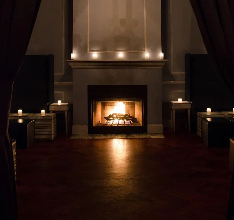 A dimly lit room highlighted by a burning fireplace.