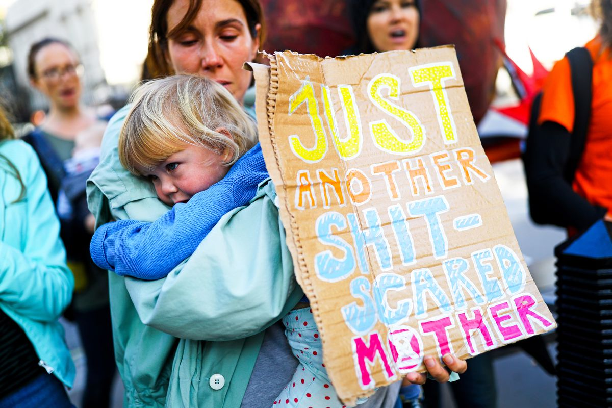 "A woman holding a child at a climate protest also holds a sign that reads, ""Just another shit-scared mother."""