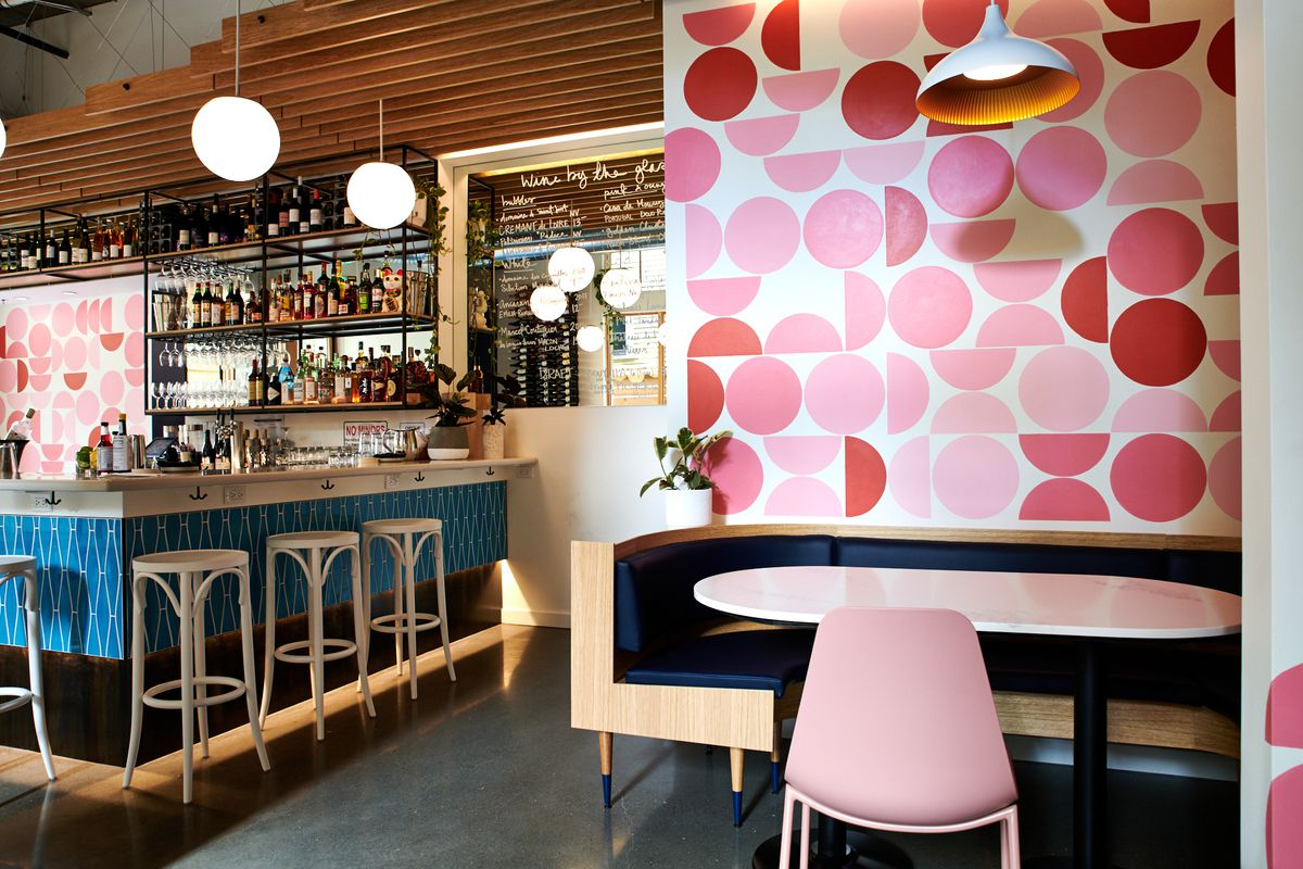 A picture of the bar at Bar Diane, which has white stools and a blue geometric pattern