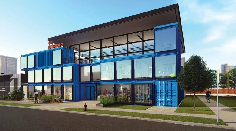 A blue building made of shipping containers with square windows and a metallic awning.