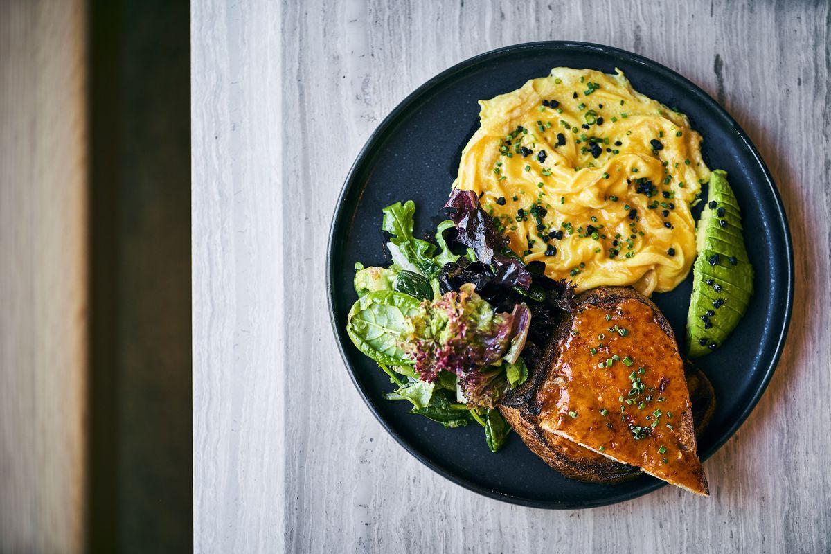 Scrambled eggs, toast, avocado on a plate.