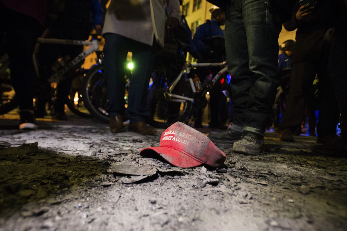 A Donald Trump slogan lies in ashes from a fire set outside the National Press Club during a protest in Washington DC on January 19.