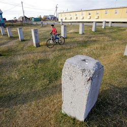 In this Sunday, Sept. 11, 2011 photo, a girl rides a bicycle in the foundation of an un-built gym in the village of Kolva near the town of Usinsk, 1500 kilometers (930 miles) northeast of Moscow. Komi is one of Russia's largest and oldest oil provinces but ruptures in aging pipelines and leaks from decommissioned oil wells make oil spills in the region routine. (AP Photo/Dmitry Lovetsky)