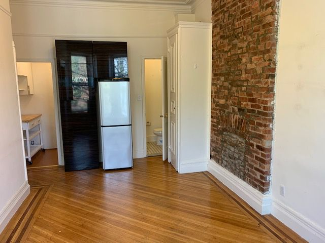 A living area with exposed brick, base moldings, and hardwood floors.