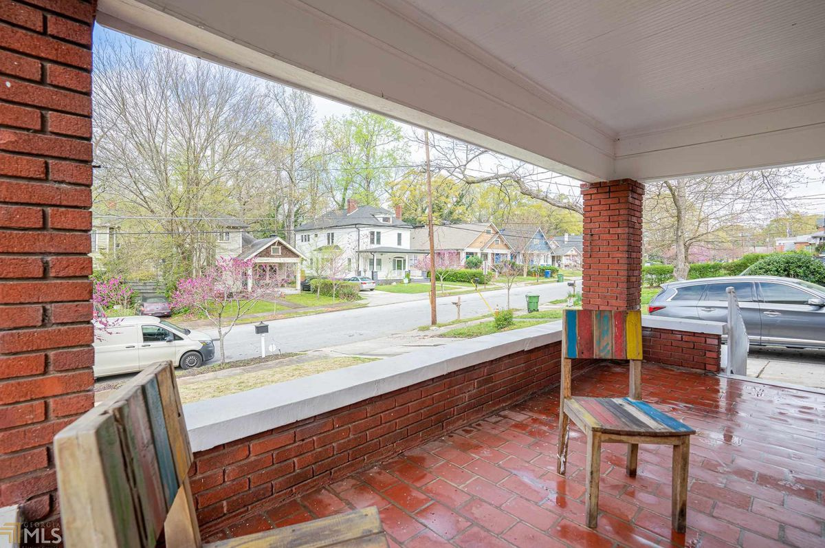 A large brick porch with many houses that are pretty across the street.