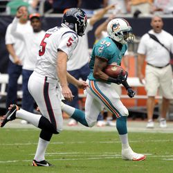Miami Dolphins running back Marcus Thigpen (34) runs past Houston Texans punter Donnie Jones (5) while returning a punt for a touchdown in the third quarter of an NFL football game on Sunday, Sept. 9, 2012, in Houston.