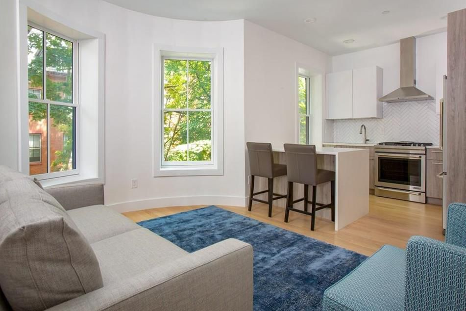 A sunny living room-kitchen area with a bay window.