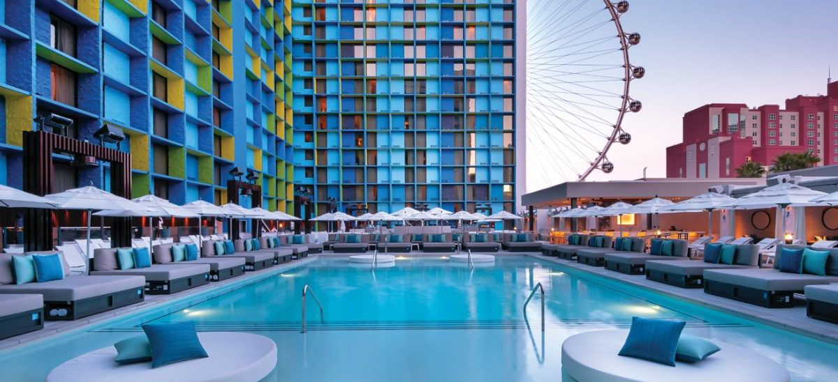 Pool beside colorful building with observation wheel in background