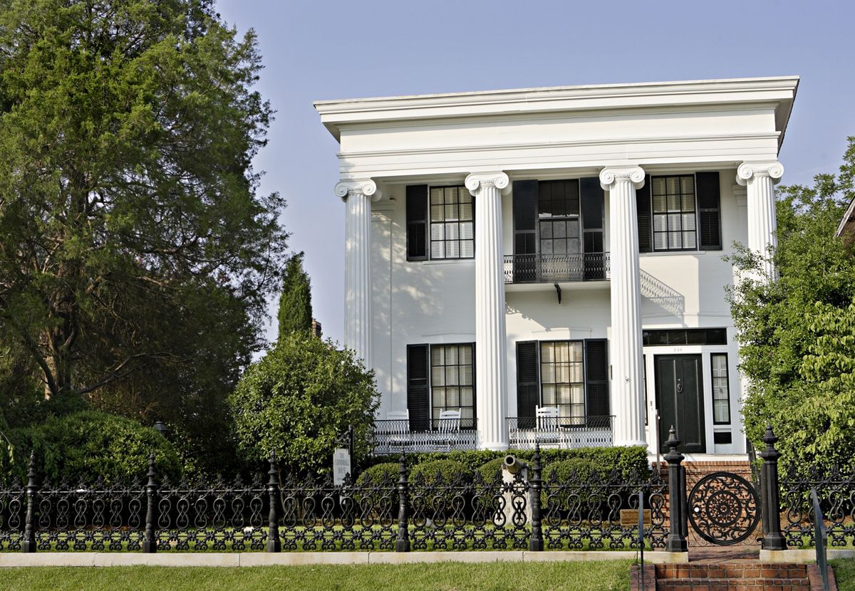 Two-story house with white columns and black wrought-iron fence out front.