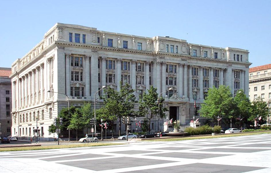 The exterior of the John Wilson Building in Washington D.C. The facade is white with multiple windows.