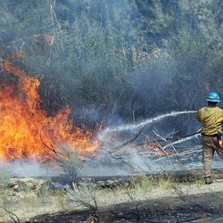Firefighters put water on flames burning in the mouth of Weber Canyon on Tuesday, Sept. 5, 2017.