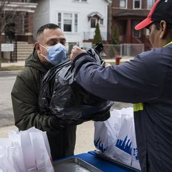 Jaime Funes, 45, receives three days of free breakfast and lunch meals for his two students at William P. Nixon Elementary School, 2121 N. Keeler Ave., Thursday morning, March 19, 2020. All Illinois schools, including Chicago Public Schools, are closed for weeks amid fears of the coronavirus pandemic.