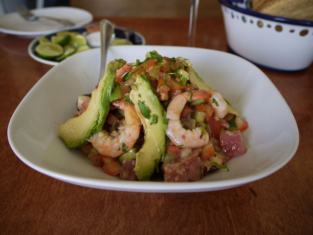 A pile of ceviche, with shrimp and slices of avocado sticking out, in a shallow bowl on a wood table with condiments and a bowl of tortillas blurred in the background