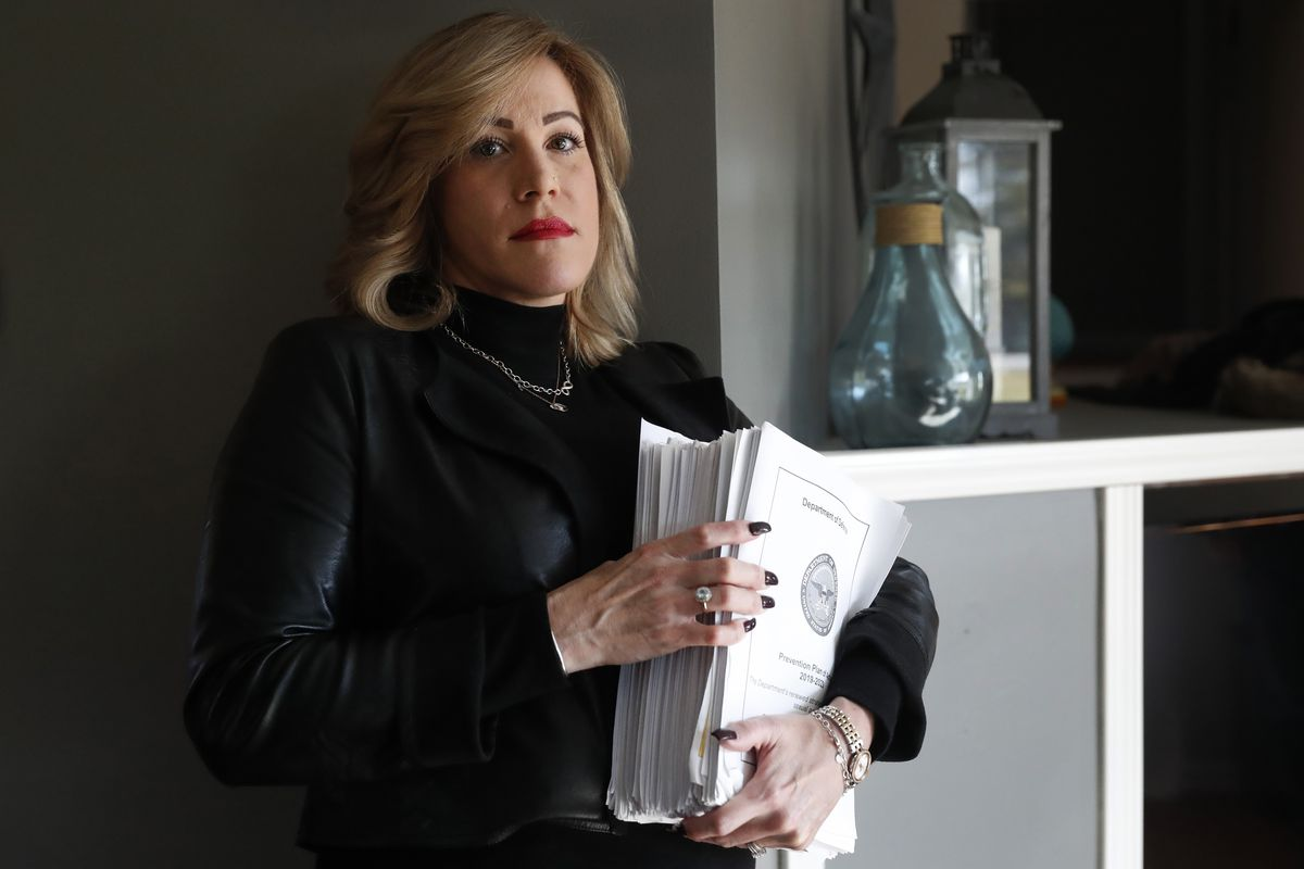 Amy Braley Franck holds a stack of papers.