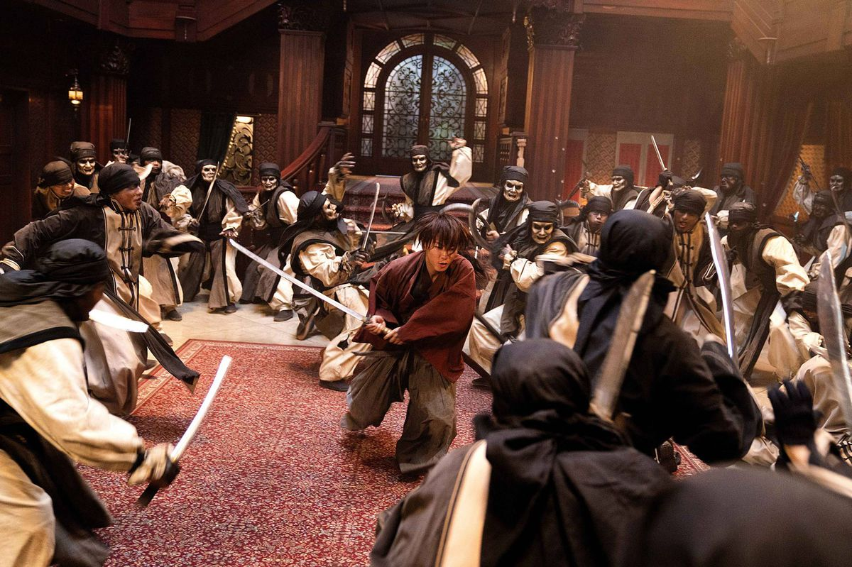 Kenshin charges through a room of masked and unmasked warriors in Rurouni Kenshin: The Final