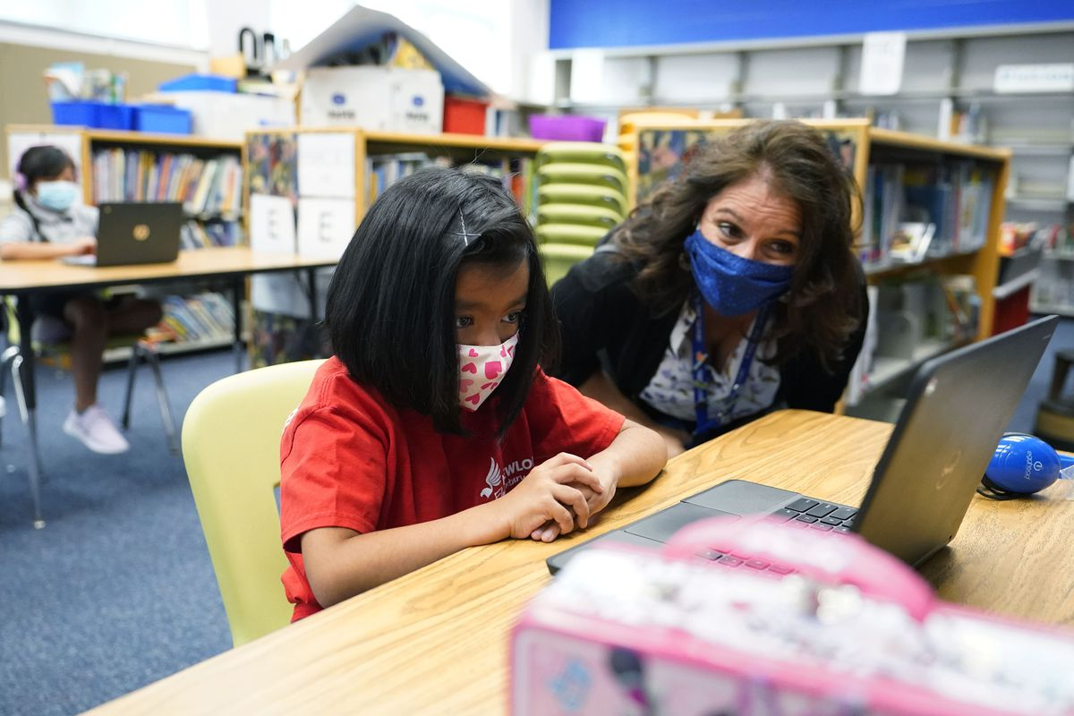 Denver Superintendent Susana Cordova talks to a masked girl working on a laptop at a learning center.