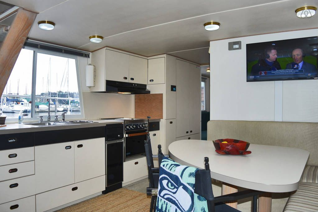 A mostly white interior of a houseboat has a football game on the TV
