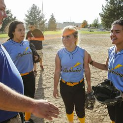Brad Thomas, left, who has been coaching his daughter's accelerated softball team for the past five years, talks with his daughter, Faith Thomas, middle, during a scrimmage at Dewey Bluth Park in Sandy, Utah, Thursday, June 9, 2016.