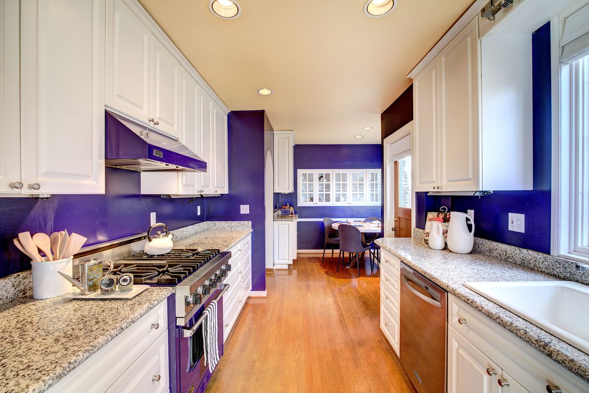 A purple-walled kitchen with an eating nook in the back