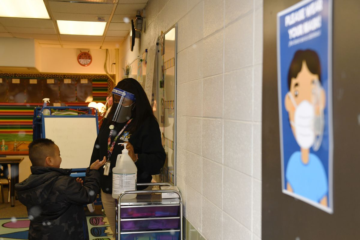 A teacher wearing a mask and face shield helps a boy sanitize his hands before class starts. A sign on the wall encourages mask wearing.