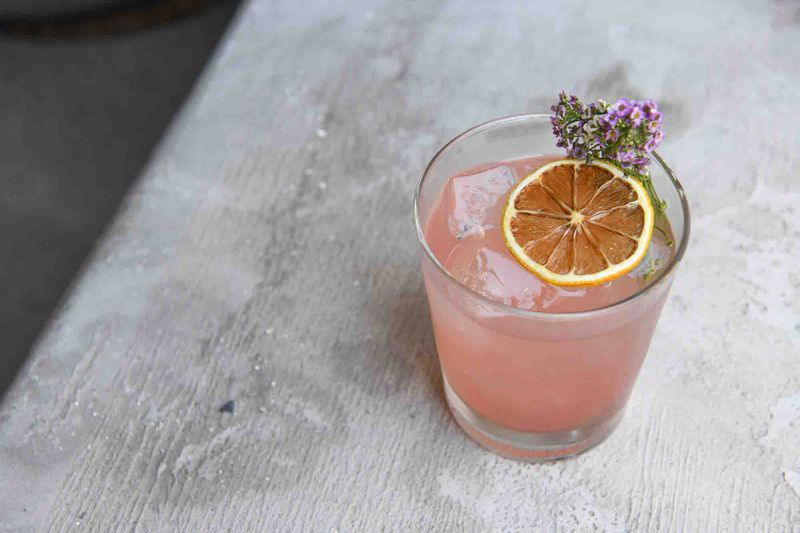 A pink tequila cocktail with dried orange rind on top.