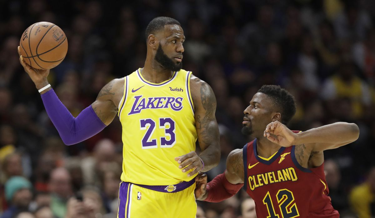 Los Angeles Lakers' LeBron James, left, looks to pass the ball as Cleveland Cavaliers' David Nwaba defends.