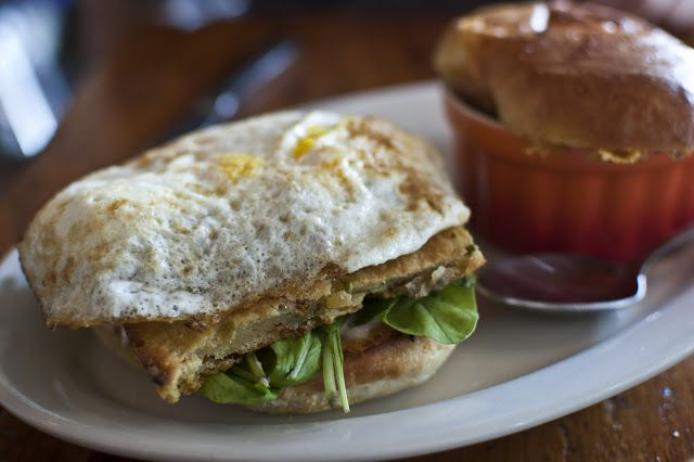 Breakfast sandwich with meat and greens, topped with an egg
