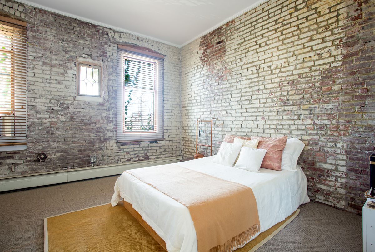 A bedroom area with a medium-sized bed, high ceilings, and exposed brick walls.