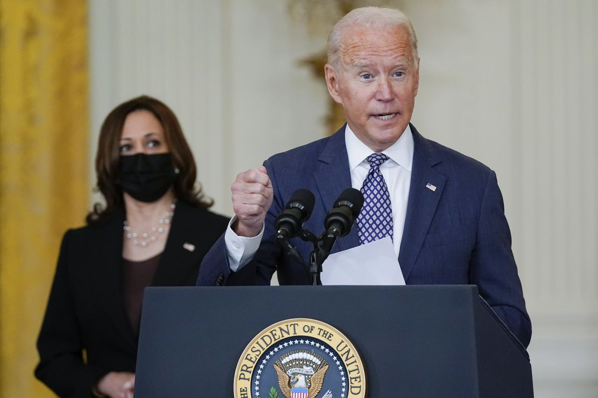 President Joe Biden speaks about the evacuation of American citizens, their families, SIV applicants and vulnerable Afghans in the East Room of the White House, Friday, Aug. 20, 2021, in Washington. Vice President Kamala Harris listens at left.