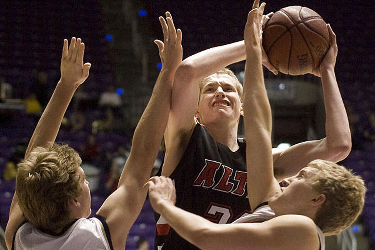 Alta's Kyle Davis makes his way around two Skyline defenders for a basket in the 5A quarterfinals in Ogden.