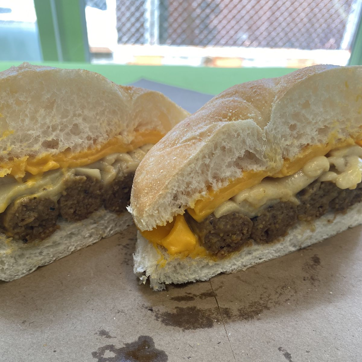 Two halves of a sausage, egg, and cheese sandwich rest on parchment paper