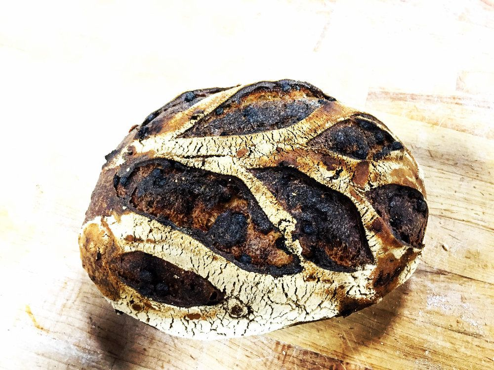 A striking dark loaf of bread with long ripples of bleached crust on a wooden surface
