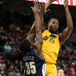 Utah Jazz forward Derrick Favors (15) passes over Denver Nuggets forward Kenneth Faried (35) at Vivint Smart Home Arena in Salt Lake City on Tuesday, Nov. 28, 2017.