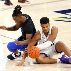 Brigham Young Cougars guard Brandon Averette (4) and Weber State Wildcats forward Dillon Jones (2) wrestle for a loose ball as BYU and Weber State play an NCAA basketball game at Vivint Smart Home Arena in Salt Lake City on Wednesday, Dec. 23, 2020. BYU won 87-79.