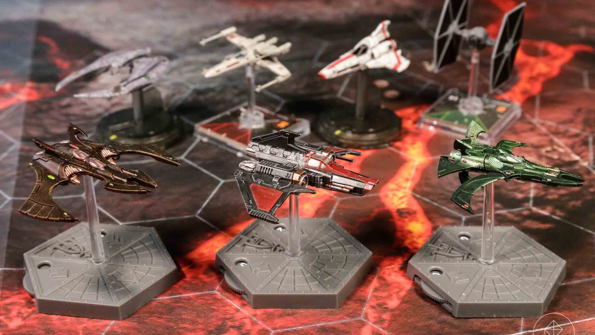 A collection of tiny plastic fighter planes, including X-Wings and 40K ships.