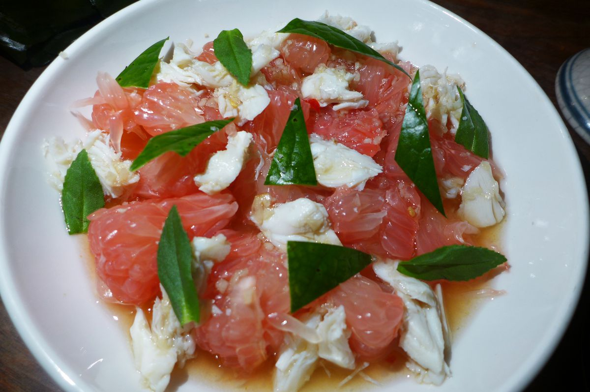 A round white bowl with chunks of pink fruit, white crab meat, and green triangular leaf cuttings.