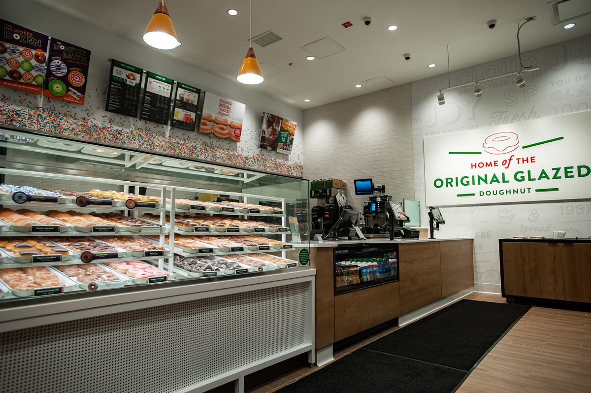 """A large glass pastry case sits beside a cash register. A sign beside it reads """"Home of the Original Glazed Doughnut."""""""