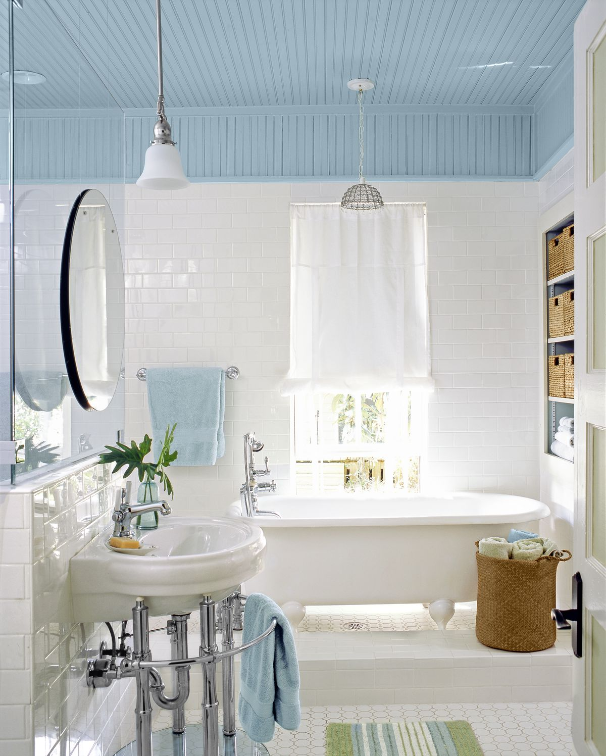 Light blue and white bathroom update with new beadboard above windows.