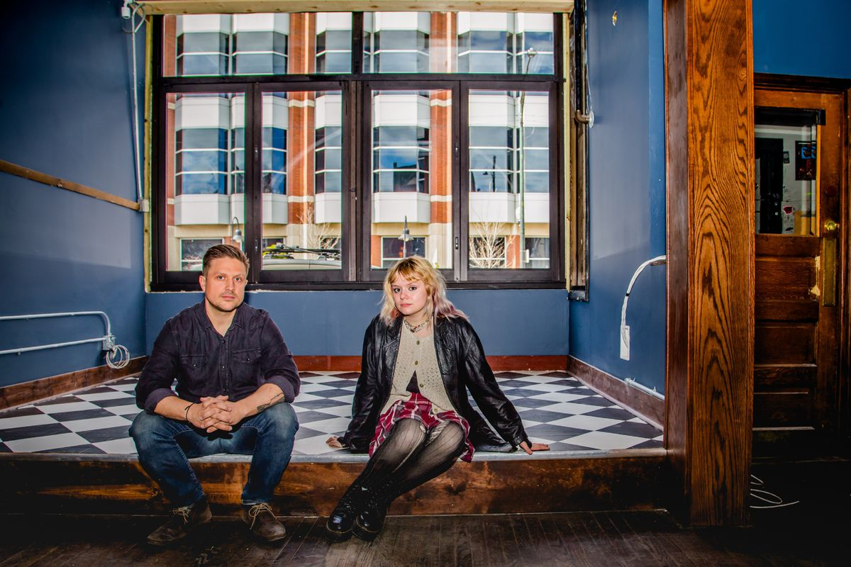 A man and woman sit on a checkerboard-tiled stage inside an old-looking building.