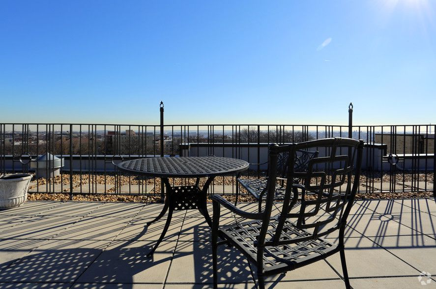 In the foreground is a chair and table and a fence on a roof deck. There is a view of Washington D.C. in the distance.