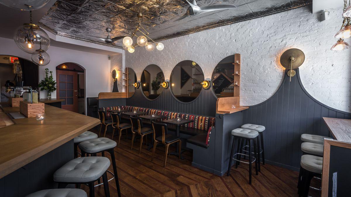 The interior of the rustic wine bar Lois with exposed white break and leather benches