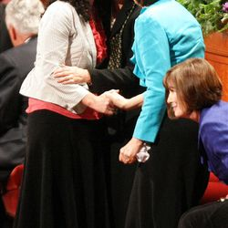 Carole M. Stephens, center, gets a hug at the end of the General Relief Society Meeting.