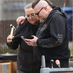 Chip and Shauncey Simpson look at a phone message as they assess their Magna yard following a 5.7 magnitude quake on Wednesday, March 18, 2020.