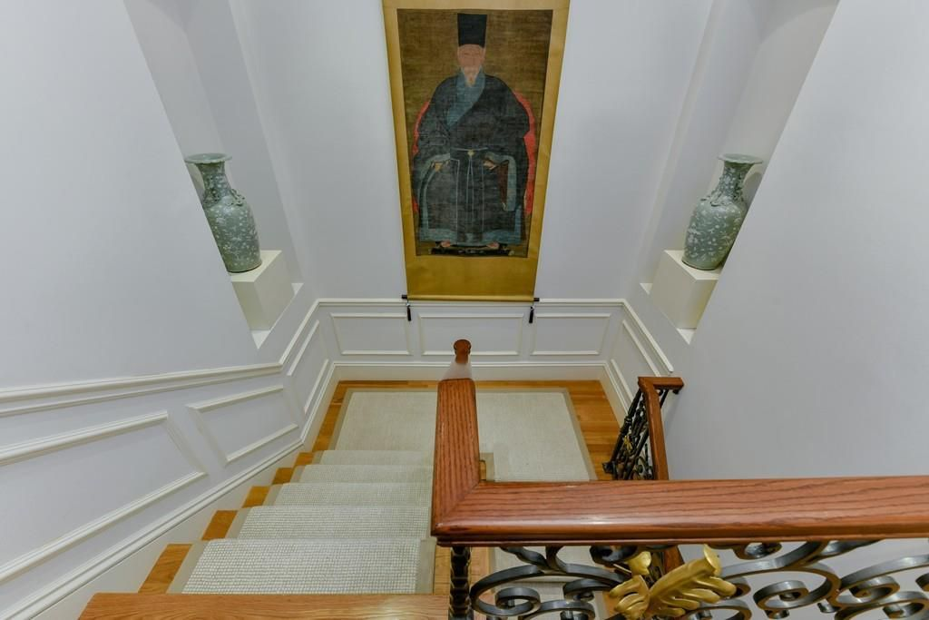An elegant staircase with a painting of a man hanging over the landing.