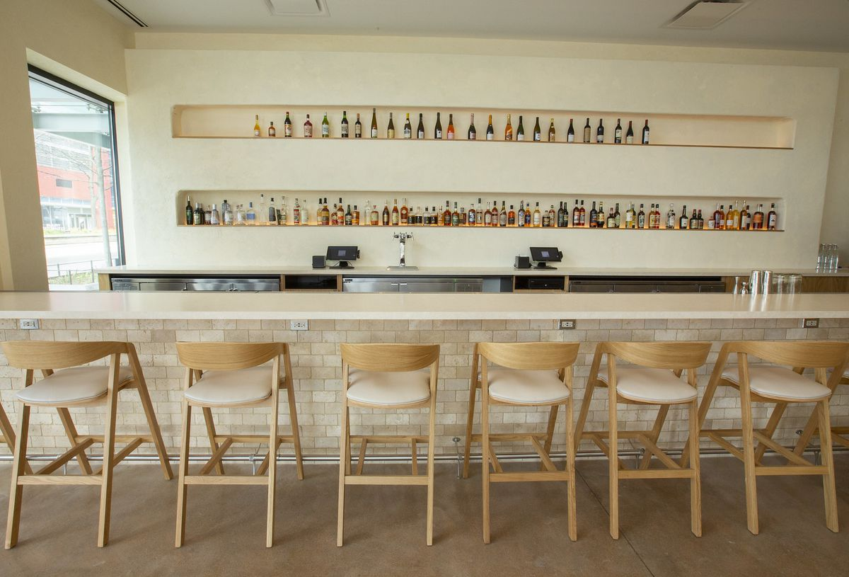A bar with light wood and fully stocked with liquor in the back.