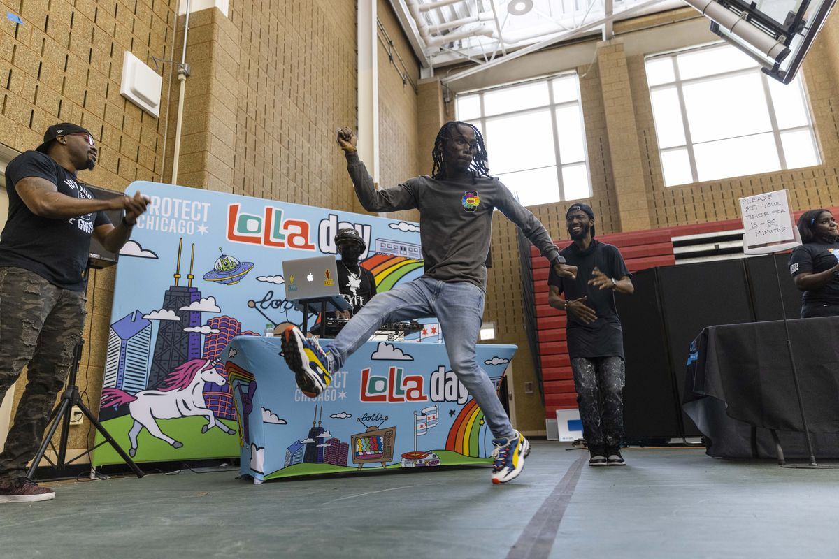 DJ Kevin Burns and Footwork Folks dancers perform for people in the observation area at a COVID-19 vaccination site at Kennedy-King College last month. Illinois reported no new COVID-19 deaths Monday for the first time in almost 16 months.