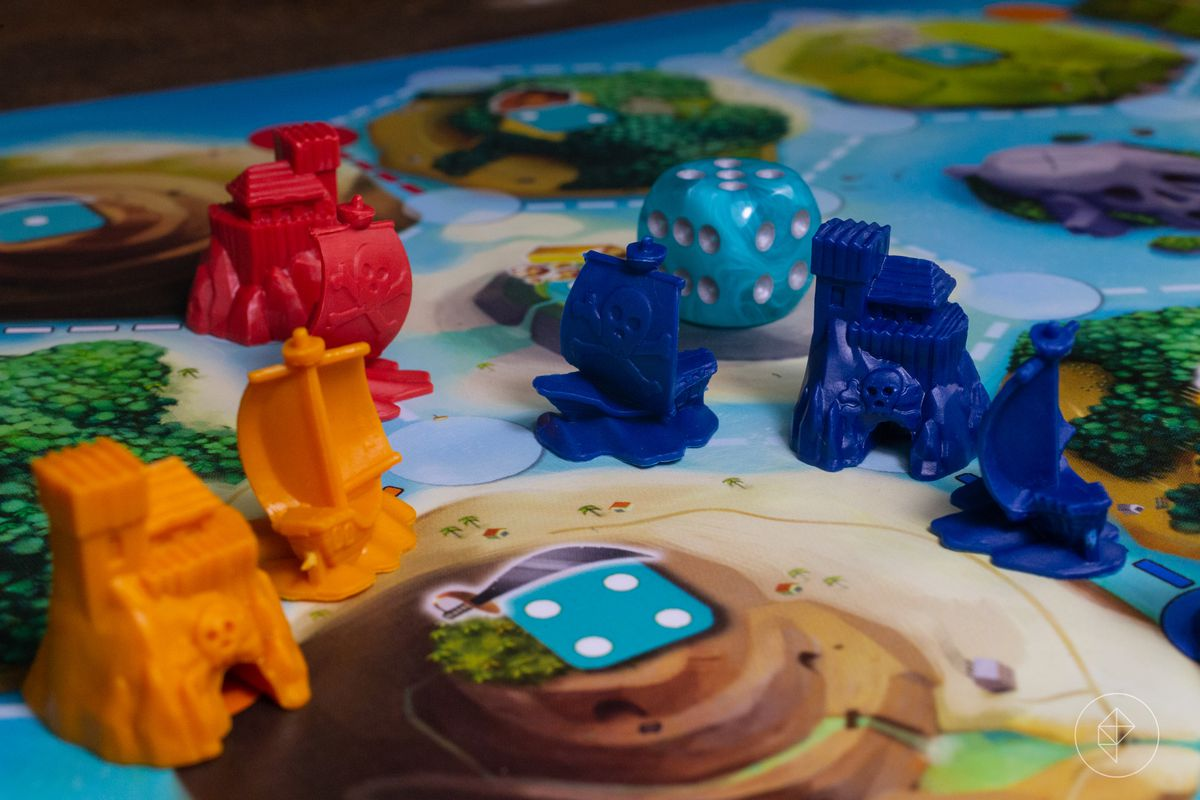 Pirate ships and secret hideouts in blue, orange, and red. A sea-colored die sits in the background.